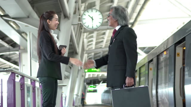 Handshake Two businessman and businesswoman at train station