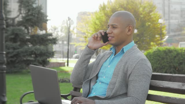 Handsome African American businessman using smart phone and laptop outdoors
