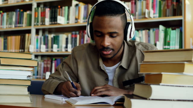 Handsome african american male student wearing headphones is listening to music sitting at table in big spacious library writing lecture surrounded by books Handsome african american male student wearing big white headphones is listening to music sitting at table in big spacious library writing lecture surrounded by books textbook stock videos & royalty-free footage