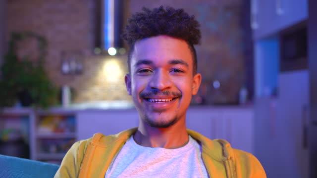 красивый афроамериканец, улыбающийся в камеру, счастливая жизнь, молодежное поколение - близко к стоковые видео и кадры b-roll