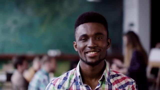 vidéos et rushes de bel homme africain au bureau moderne occupé. portrait de jeune homme réussi caméra en regardant et en souriant. lente mo - profession supérieure ou intermédiaire