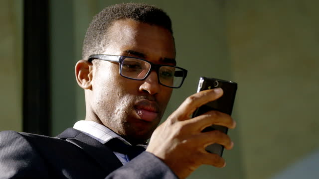 handsome African-american businessman texting messages on his smartphone video