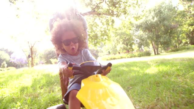 Bonito-americano africano pai e filho brincando com um Carro de pedal - vídeo