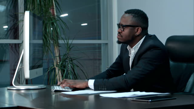 handsome afro-american businessman working and typing on laptop in the office - indennità video stock e b–roll