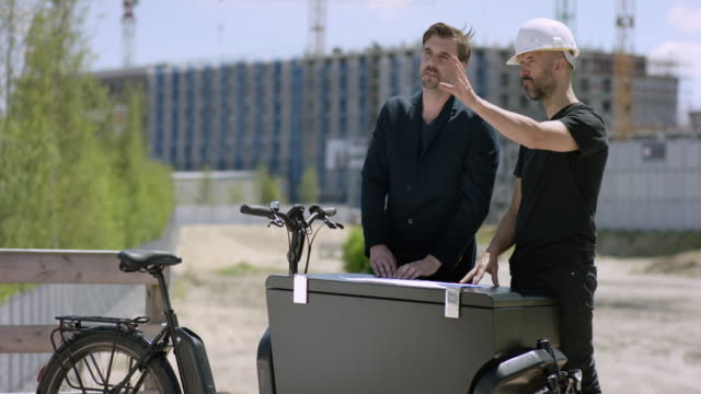 Handsome Architect and construction worker discussing building plans on a cargo bike video