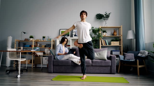 Handsome Asian man doing yoga practice while girlfriend working with laptop
