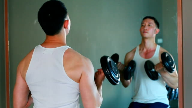 Handsome asian man is playing dumbbell infant of mirror-reflection and distortion