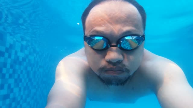 Handsome asian man underwater video shot Close-up footage of a young man swimming and wearing eye goggle. competition group stock videos & royalty-free footage
