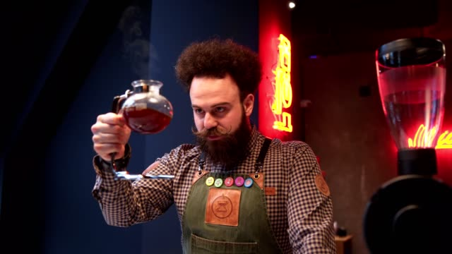 Handsome bearded barista holding a bowl filled with coffee