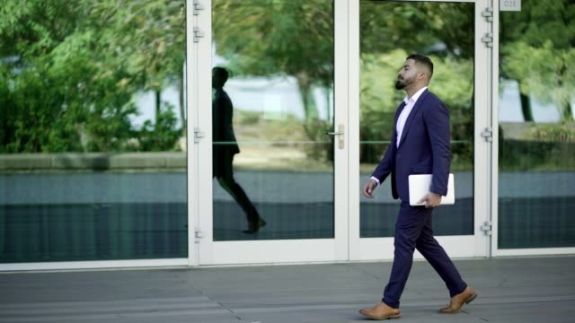 Handsome bearded businessman walking with laptop on street
