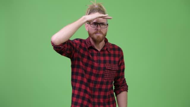 Homem farpado considerável do hipster com dreadlocks que procurara algo - vídeo