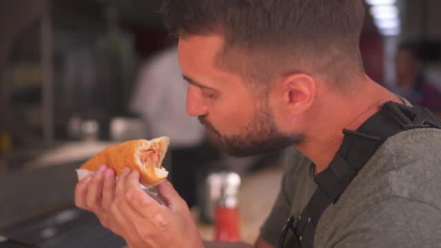 vídeos de stock, filmes e b-roll de cachorro bonito homem barbudo comendo no café - cachorro quente