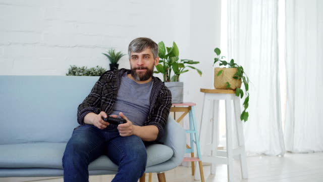 vídeos de stock e filmes b-roll de handsome bearded man wearing casual clothes is playing video game sitting on couch at home. modern technologies, happy people and leisure time concept. - man joystick