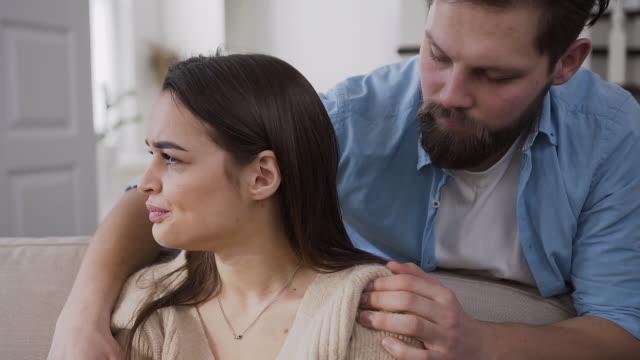 stilig skäggig ung man försöker lugna sin upprörda olyckliga flickvän och kramar henne ryggen - flickvän bildbanksvideor och videomaterial från bakom kulisserna