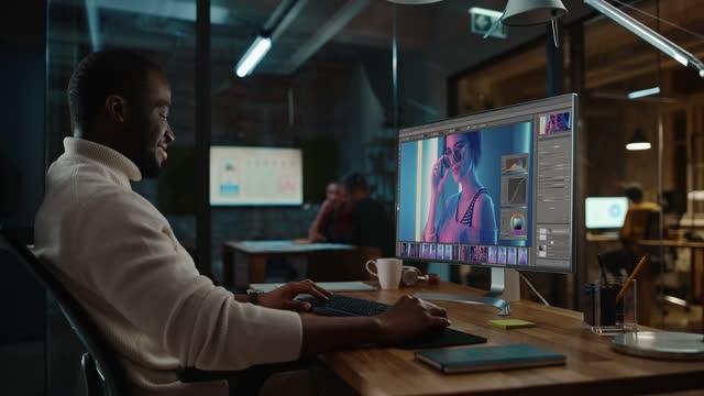 bello specialista afroamericano nero che lavora su computer desktop in ambiente ufficio creativo. hipster male sta modificando una fotografia di moda con modello in un software di editing grafico digitale. - fotografia immagine video stock e b–roll