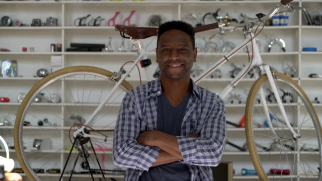 handsome black business owner of a bicycle shop looking at the camera smiling with arms crossed - small business owner stock videos & royalty-free footage
