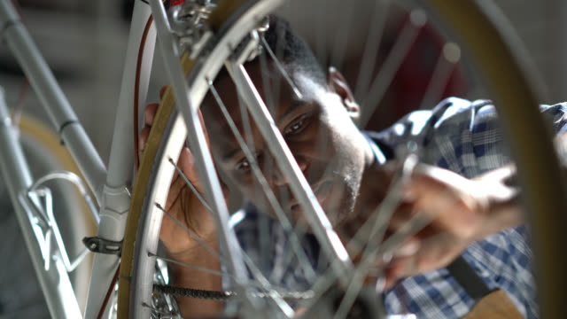 Handsome black man adjusting the back wheel of a bicycle at a repair shop