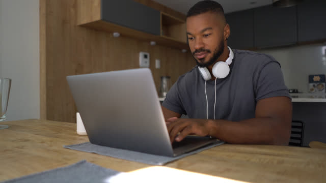 handsome black man working on his laptop wearing his headphones on neck looking focused - usare il laptop video stock e b–roll