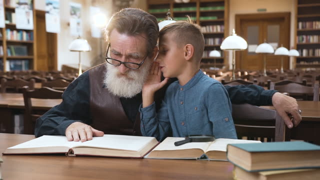 handsome blond boy whispering to his experienced old grandfather which sitting in the library - ear talking video stock e b–roll