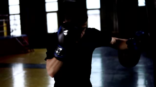 Handsome boxer punches the heavy bag while wearing black gloves. Sport, boxing ring background