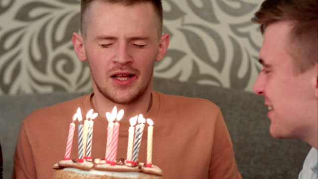 Handsome boy dreamsabout his wish and blows out candles on birthday cake and drinks orange juce video