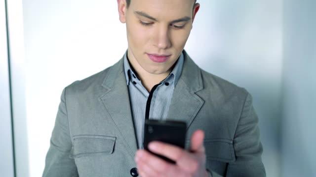 bello ragazzo look al telefono - blazer video stock e b–roll