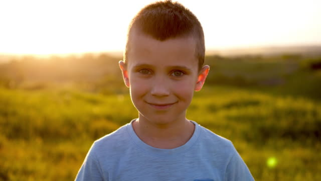 Handsome boy posing at camera on sunset in field