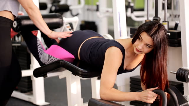 Handsome brunette does exercises on block training apparatus for legs video