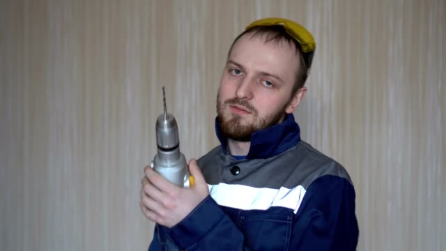 Handsome builder in uniform with tool belt holding drill. Bearded young man working drill