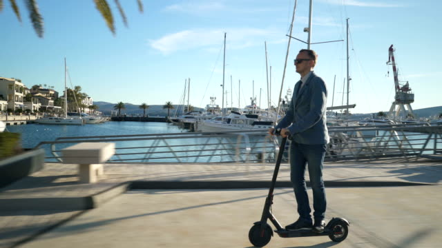 handsome business guy driving on scooter gadget along the yacht mooring. - monopattino elettrico video stock e b–roll