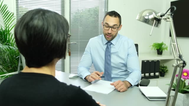 handsome business man with female client signing contract agreement and shaking hands in office handsome business man with a female client signing contract agreement and shaking hands in office mortgages and loans stock videos & royalty-free footage