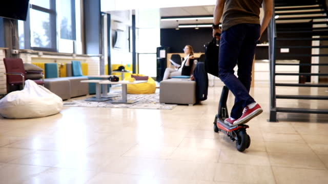 handsome businessman entering the office on his scooter - monopattino elettrico video stock e b–roll