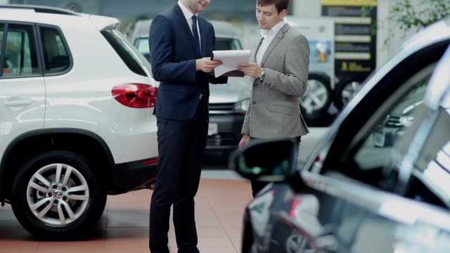 Handsome businessman is going to buy a new car