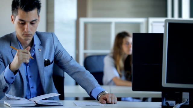 Handsome businessman is making notes sitting in office video
