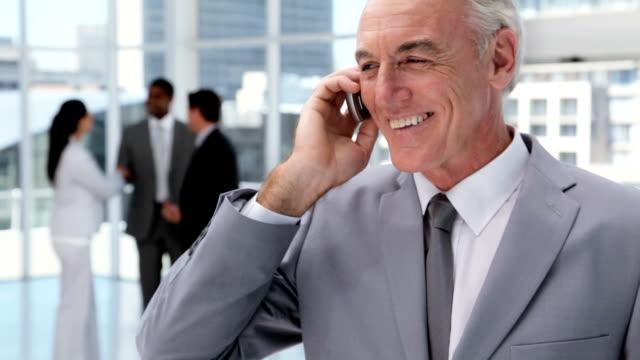 przystojny biznesmen na telefon komórkowy w biurze holu - siwe włosy filmów i materiałów b-roll