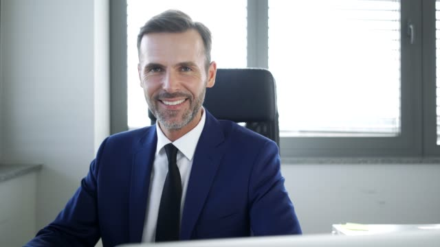 handsome businessman sitting in office and smiling at camera - affidabilità video stock e b–roll