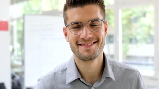 Handsome businessman smiling in new office Dolly shot of handsome businessman smiling. Close-up portrait of confident male professional is in office. He is wearing eyeglasses. mid adult stock videos & royalty-free footage