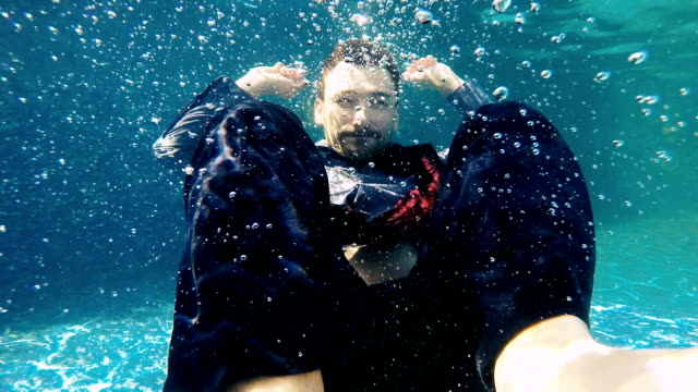Handsome businessman swims under water in suit video