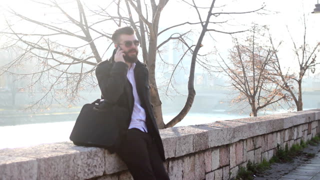 Handsome businessman talking on  phone outdoors video
