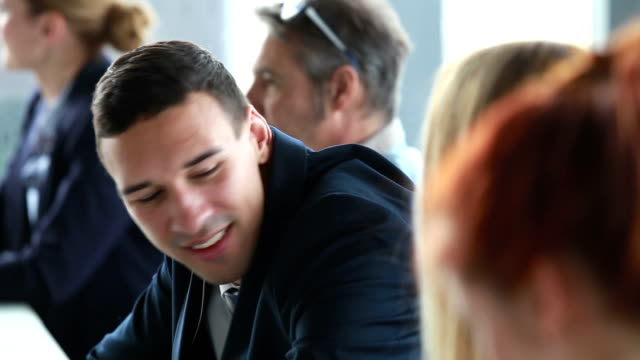 Handsome businessman talking with female colleagues at conference table video