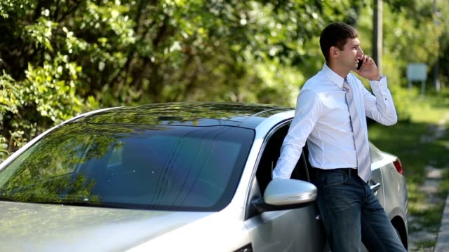 Handsome businessman using mobile phone near car Handsome young businessman in necktie talking on smartphone while leaning on parked car over rural landscape background. Successful entrepreneur in formal wear communicating with business partner using mobile phone outdoors during business road trip. leaning stock videos & royalty-free footage
