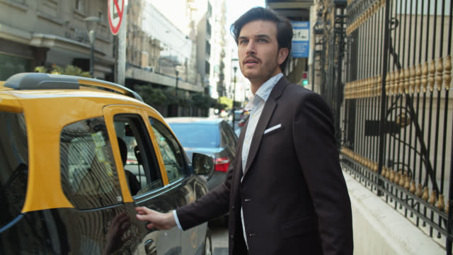 Handsome Businessmen Getting Out of Taxi on Buenos Aires Street video