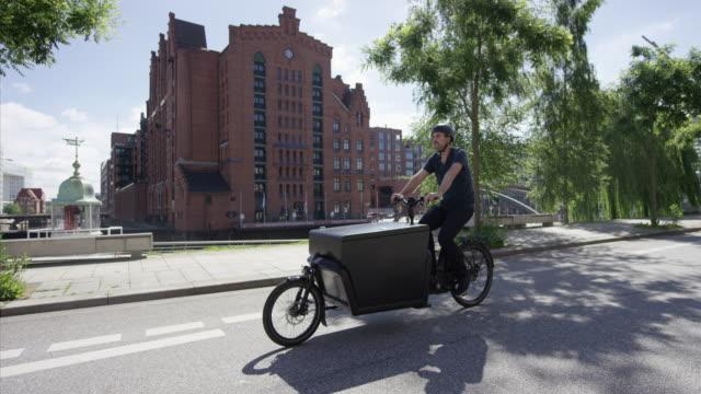 vídeos de stock e filmes b-roll de handsome cargo bike courier is cycling on a street - green city