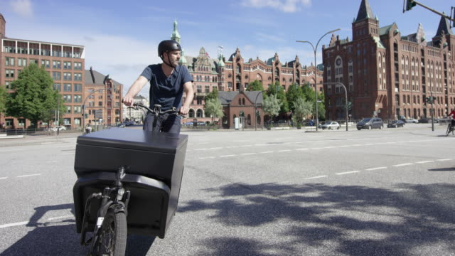 Handsome cargo bike courier is cycling on a street video