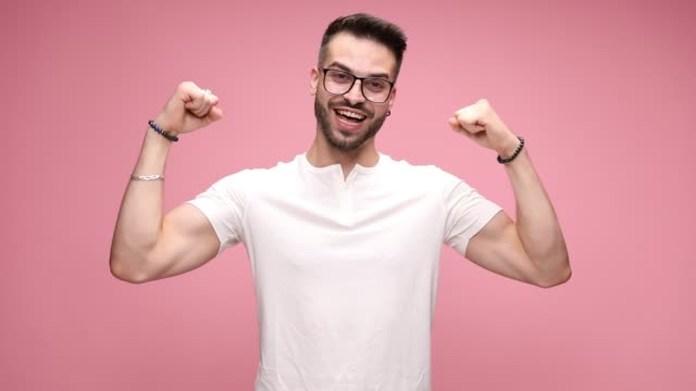 handsome casual man wearing a white t-shirt and eyeglasses, standing with arms crossed against pink background, looking down then looking at camera, smiling then raising his fists up on pink background - maglietta bianca video stock e b–roll