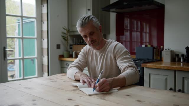 vídeos de stock, filmes e b-roll de homem branco bonito em casa escrevendo em seu diário - escrever