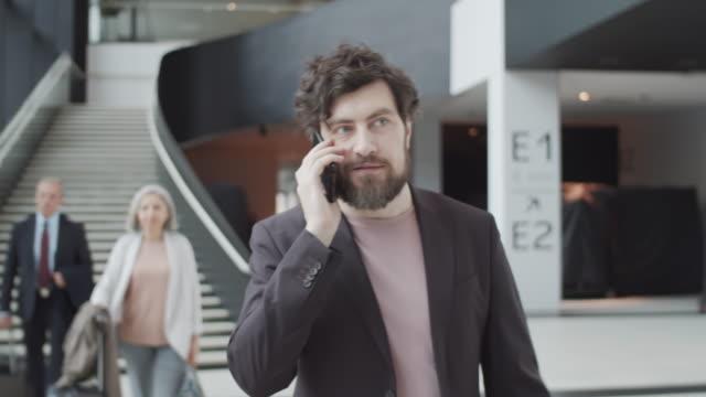 stockvideo's en b-roll-footage met knappe kaukasische mens die door luchthaven loopt en op telefoon spreekt - men blazer