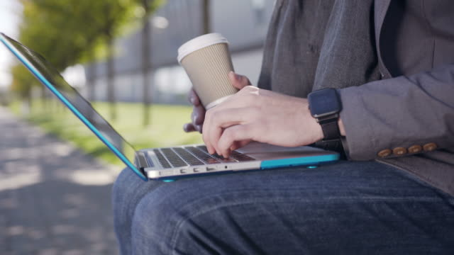 Handsome caucasian young man dressed in jacket and scarf, sitting on the bench with laptop and a coffee typing text on keyboard. Outdoor