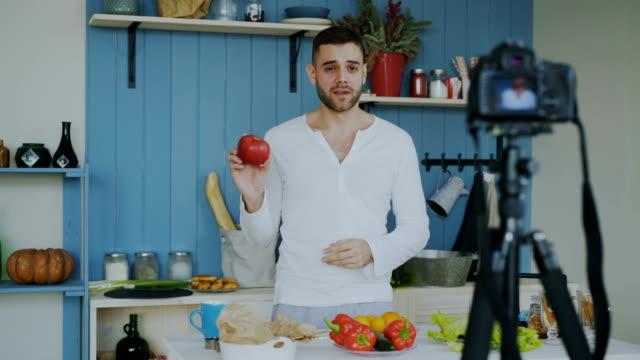 vídeos de stock, filmes e b-roll de homem bonito alegre, gravação de vídeo blog sobre comida saudável vegetariana na câmera dslr na cozinha em casa - blogar