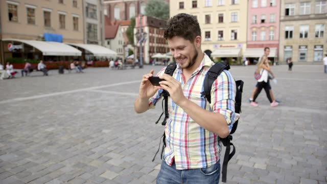 Handsome cheerful man taking photo with mobile phone in the city.. video